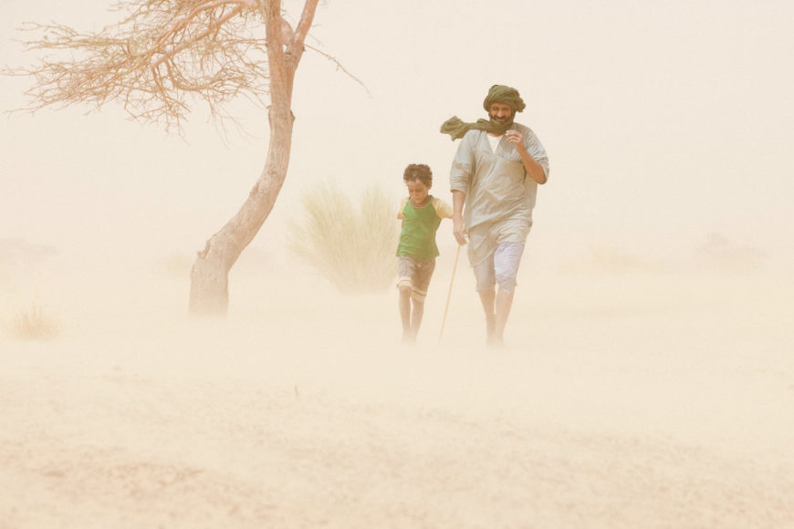 Mauritania,-Adrar---father-and-son-walking-trhough-a-sandstorm-in-the-desert