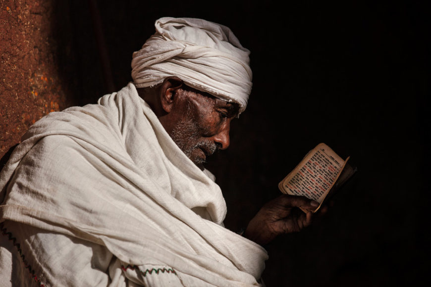 Priest-reading-from-the-bible-on-a-morning-at-Lalibela,-Ethiopia